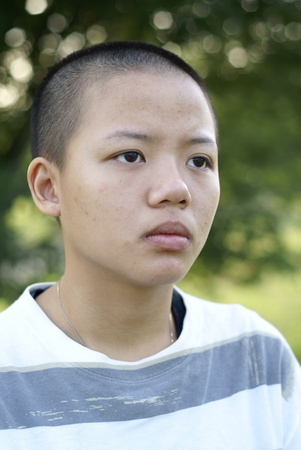 Depressed asian teen girl with shaved head photo