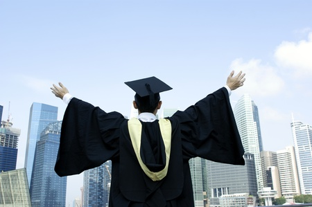backview: Graduate outstretched arms with urban city