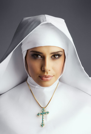 make belief: Close up Portrait of young nun on gray background with blue cross on neck Stock Photo
