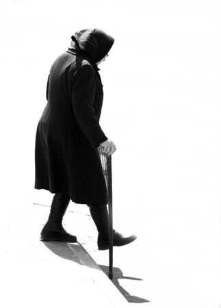A silhouette of an old woman dressed in black stepping down
