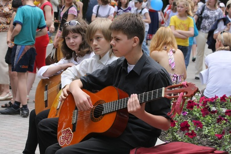 talent show: Guitar trio performance,Ukraine - JUNE 2010. Young guitar players perform in a local park on Childrens Day