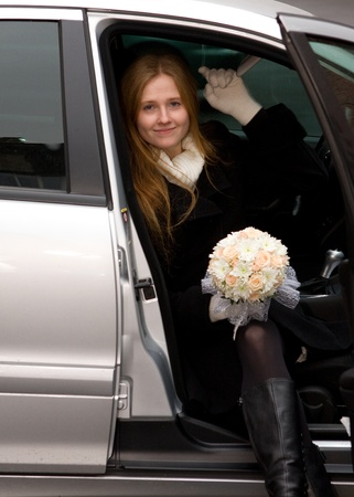 fiancee: a young fiancee in a car with a wedding bouquet Stock Photo