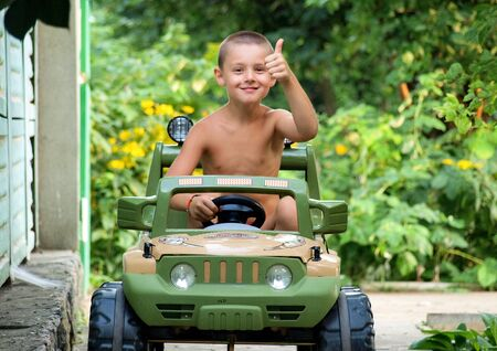 pre schooler: six-year boy making fun by driving  a car