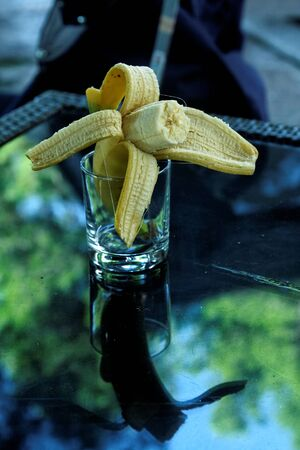 Banana in the glass on a dining table Stock Photo