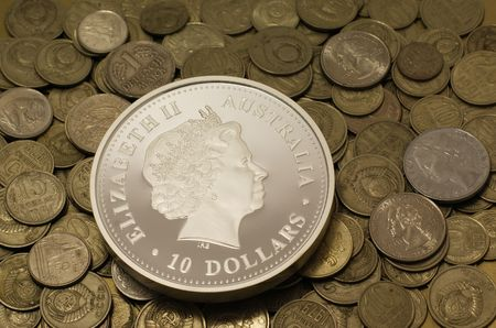 Big silver collection coin with different poor coins on background