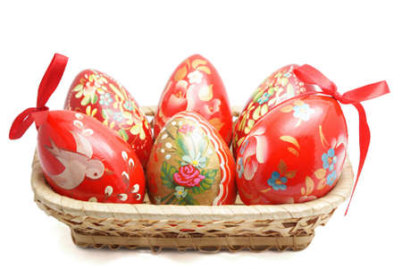 Hand painted Easter eggs in wicker basket isolated on white background photo