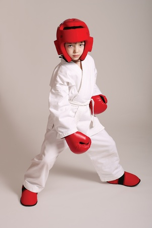 Young boy in kimono ready to fight on grey background Stock Photo - 9997159