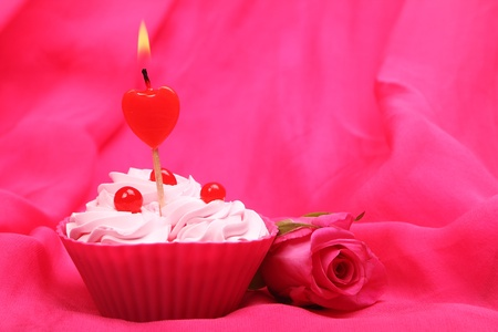 Tasty anniversary cupcake with candle, on pink background photo
