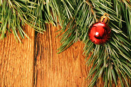 Old wooden background with pine branch and Christmas ball photo