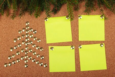 Thumb tacks in shape of Christmas tree on cork board photo