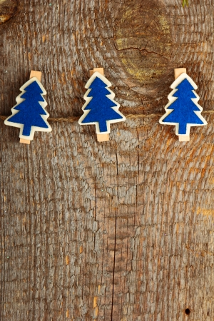 Clothes-peg in shape of Christmas tree on old wooden background photo