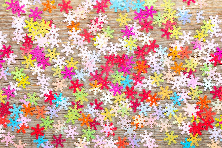 Multicolored little snowflakes on old wooden background photo