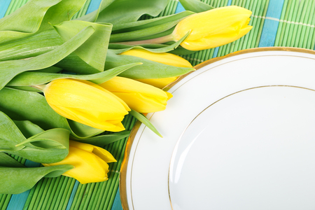 Fresh yellow tulips and white plate on green  bamboo placemats photo