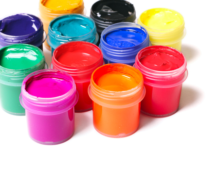 Jars full of multicolor paints on white background photo