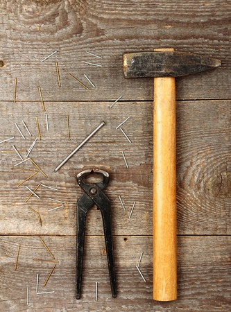 pinchers: Old big hammer on brown wooden background Stock Photo