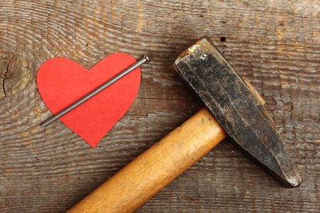 Red cardboard heart with big nail on wooden background photo