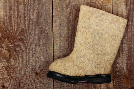 valenki: Russian traditional winter felt boot valenki on wooden background Stock Photo