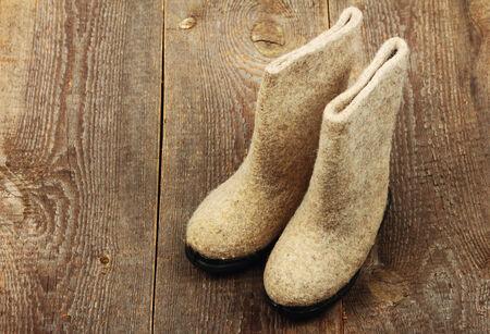 Russian traditional winter felt boot valenki on wooden background. Stock photo Stock Photo