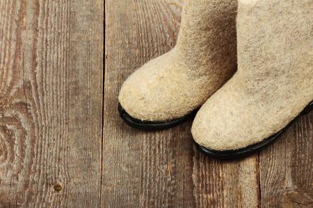 valenki: Russian traditional winter felt boot valenki on wooden background. Stock photo Stock Photo