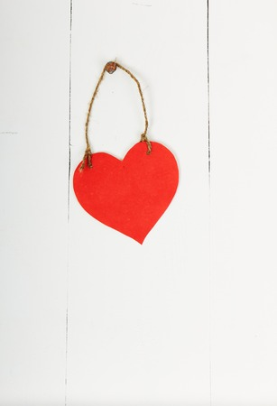 Empty cardboard heart hanging with string and nail, on wooden background, painted with white color photo