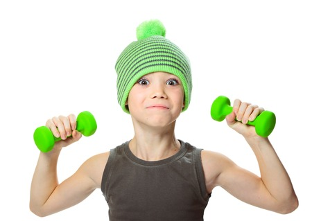 seven years: Seven years boy is doing exercises to develop muscles isolated on white background