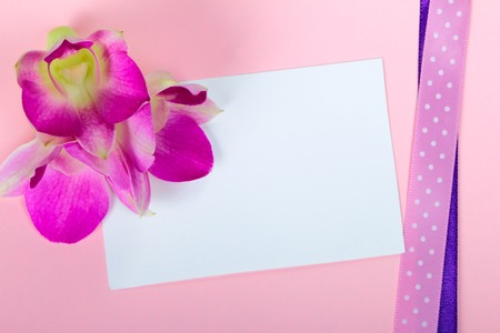 Empty greeting card with orchid flowers on pink background photo