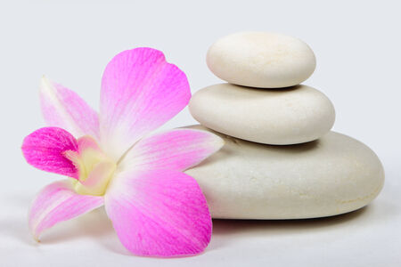 Pyramid of the stones with orchid on grey background photo