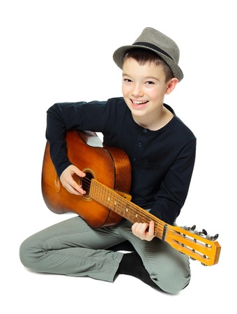 boy playing guitar: Portrait of eleven years old boy playing guitar on white background