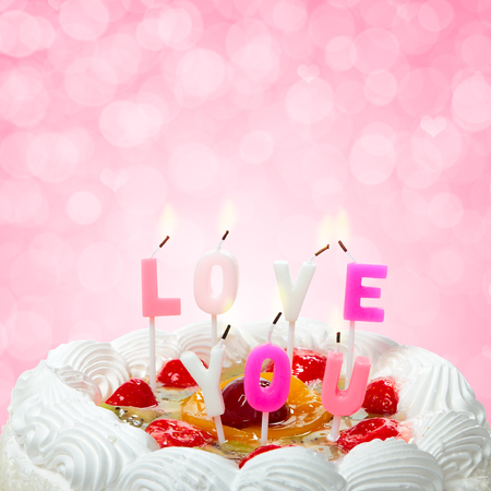 Valentines cake with candles on abstract background. Love you. photo