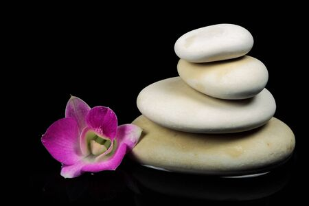 Spa stones in the water with orchid on black background photo