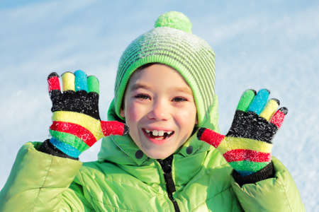 colrful: Green hat and jacket clothing boy with colorful gloves on snow background
