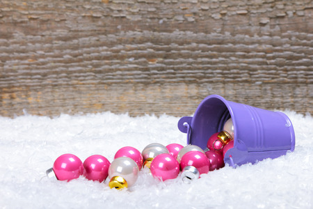lillac: The bucket with scattered Christmas balls on snow with wooden background