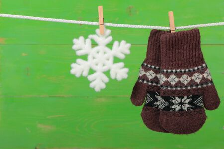Mittens with snowflakes hanging on the clothesline on green wooden background  Stock Photo