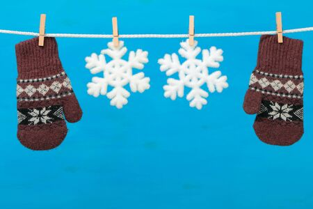 Mittens with snowflakes hanging on the clothesline on blue wooden background