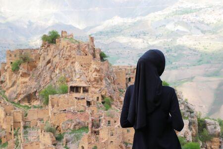 Femme musulmane en hijab debout sur la montagne et regardant vers le Gamsutl. République du Daghestan, Russie. Concentrez-vous sur la femme.