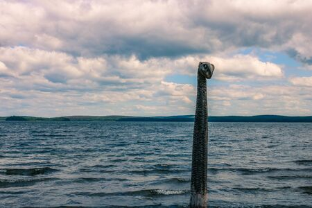 An old wooden sea monster totem against the backdrop of a lake among a green forest under the cloudy sky of Siberia.