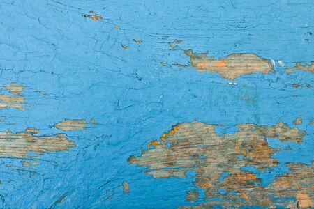 Piece of old painted boat with blue peeling and scratched paint over a traditional wooden boards Banque d'images