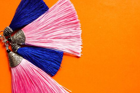 Earrings with blue and pink tassels lying on the orange background.