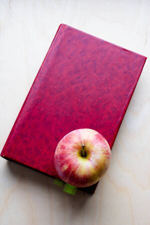 Red apple with a red hard cover book on wooden background. Apple of knowledge.