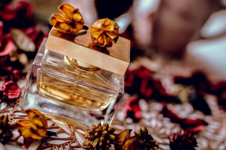 Perfume bottle and red roses on wooden table. Dynamic photo.