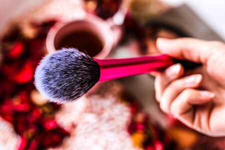 Woman hand holding makeup brush. First-person view. Stock Photo