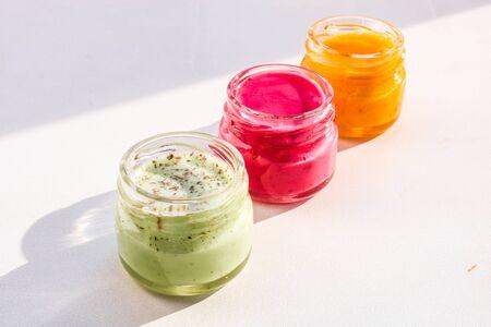 Three jars full of multi colored honey souffle , mix taste.