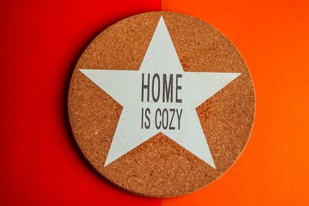 Top view of round cork trivet on colorful red and orange background. Home is Cozy.