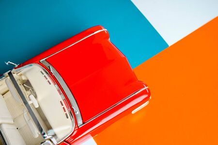 Classic car with close up shot view from above. Colorful blue, orange, white and red bacground. Concept whith scale car model.