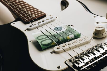 Play for money with guitar and cash. Music and money concept. One hundred euros. Banque d'images - 129037193