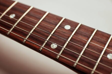 Guitar fretboard close up top view of an electric guitar neck and strings on white background isolated. Banque d'images - 129037195