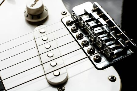 Part of modern electric six string guitar black and white color with glossy finish, pickups and control knobs close up view. Banque d'images - 129037327
