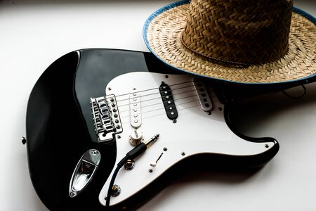 American culture. Country music concept theme with a cowboy hat and electronic guitar on a white background. Banque d'images - 129037352
