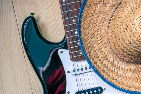 American culture. Country music concept theme with a cowboy hat and electronic guitar on wooden background. Banque d'images - 129037356