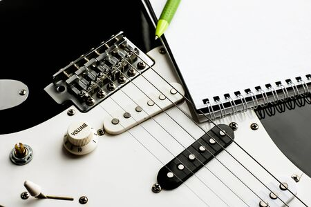 Top view of instrument music recording background concept.Flat lay the pen and notepad on classic guitar at home studio.